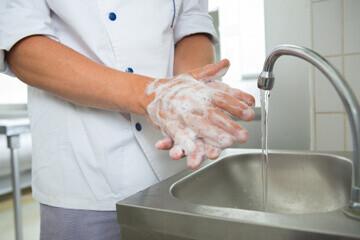 Personnel de cuisine respectant les règles d'hygiène en se lavant les mains