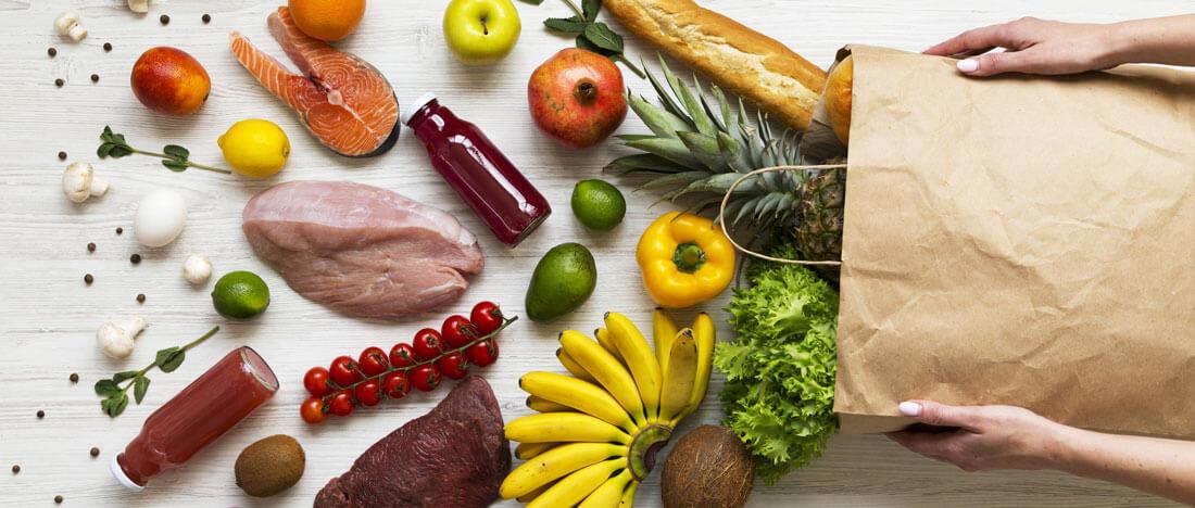 Produits frais de types viande, poisson, fruits et légumes sortis d'un sac en papier