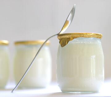 Pot de yaourt à l'ancienne avec une cuillère posée dessus
