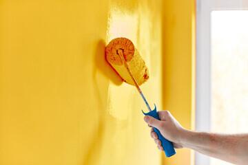 Passage d'une peinture d'ambiance alimentaire de couleur jaune au rouleau sur un mur