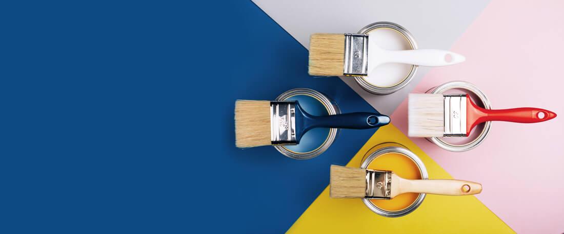 Différent pots de peinture de couleurs bleu, jaune, rose et blanche avec pinceau dessus pour peinture alimentaire
