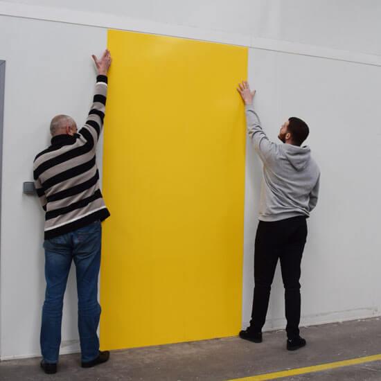 Personnes posant une plaque de PVC jauen comme revêtement mural dans une cuisine professionnelle