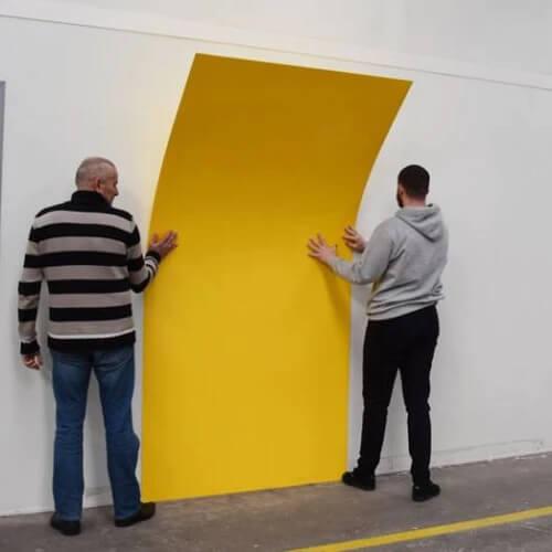 Deux personnes en train de poser une plaque de PVC jaune comme revêtement mural dans une cuisine professionnelle