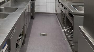 Zoom sur la bouche d'évacuation au milieu du sol d'une cuisine professionnelle