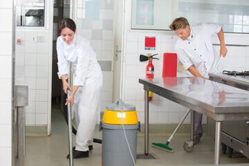 Personnel de cuisine nettoyant un sol de cuisine professionnelle