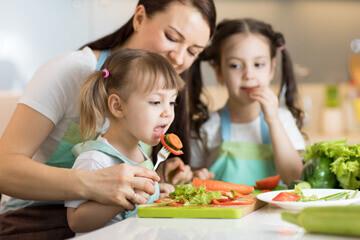 Mère et ses deux filles dégustant des fruits et des légumes