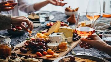 Planche de fromages et raisin et personnes buvant du rosé