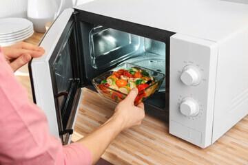Personne plaçant un plat cuisiné dans un micro-ondes