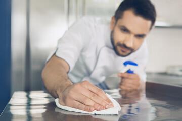 Vue d'une personne nettoyant un plan de travail en inox alimentaire avec un chiffon doux