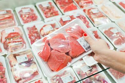 Personne montrant de la viande emballée dans un supermarché
