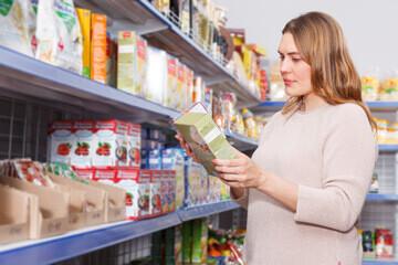 Femme lisant l'étiquette d'un produit dans  un supermarché