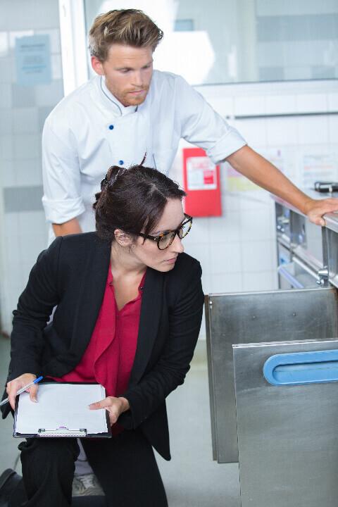 Inspectrice contrôlant le respect des règles d'hygiène dans le frigo d'un restaurant